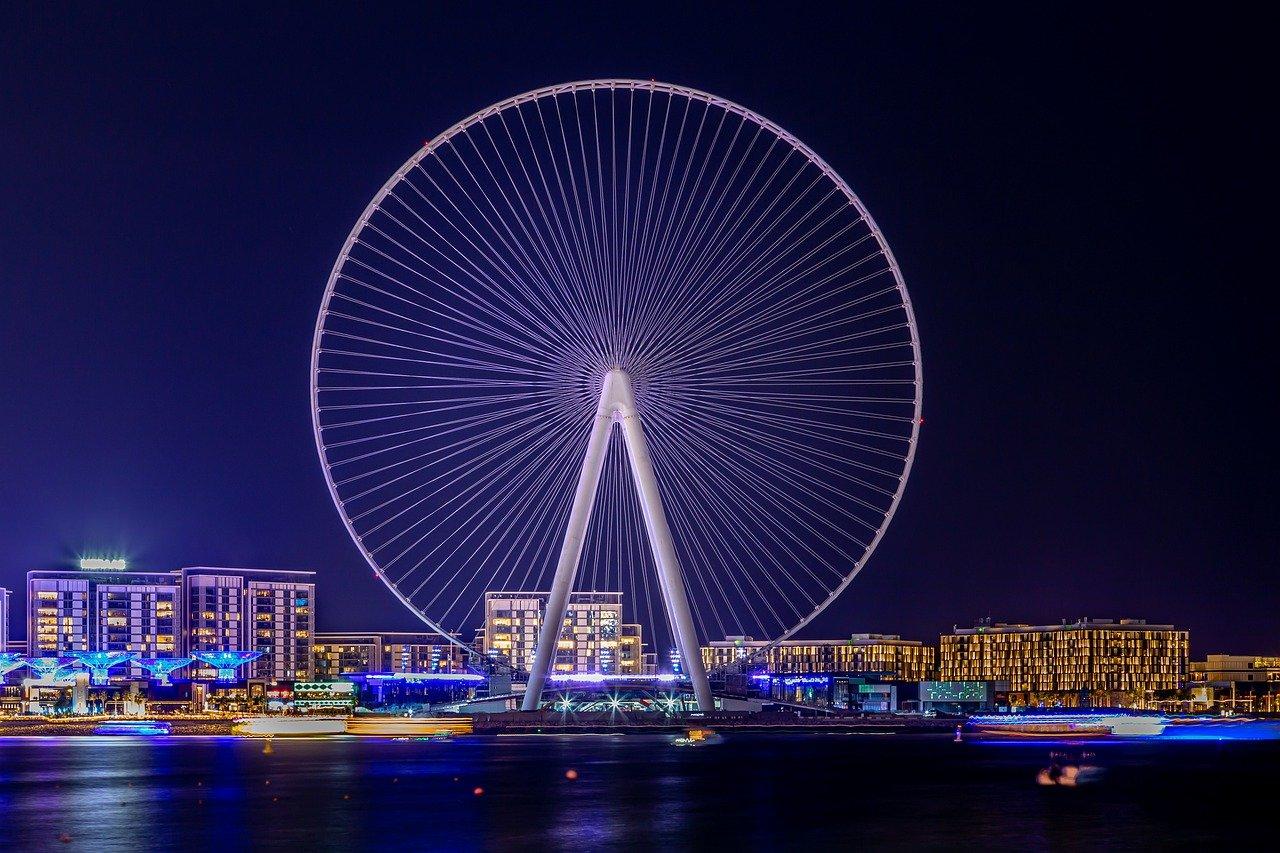 Expo 2020 de Dubaï - grande roue illuminé vue de nuit sur l'eau